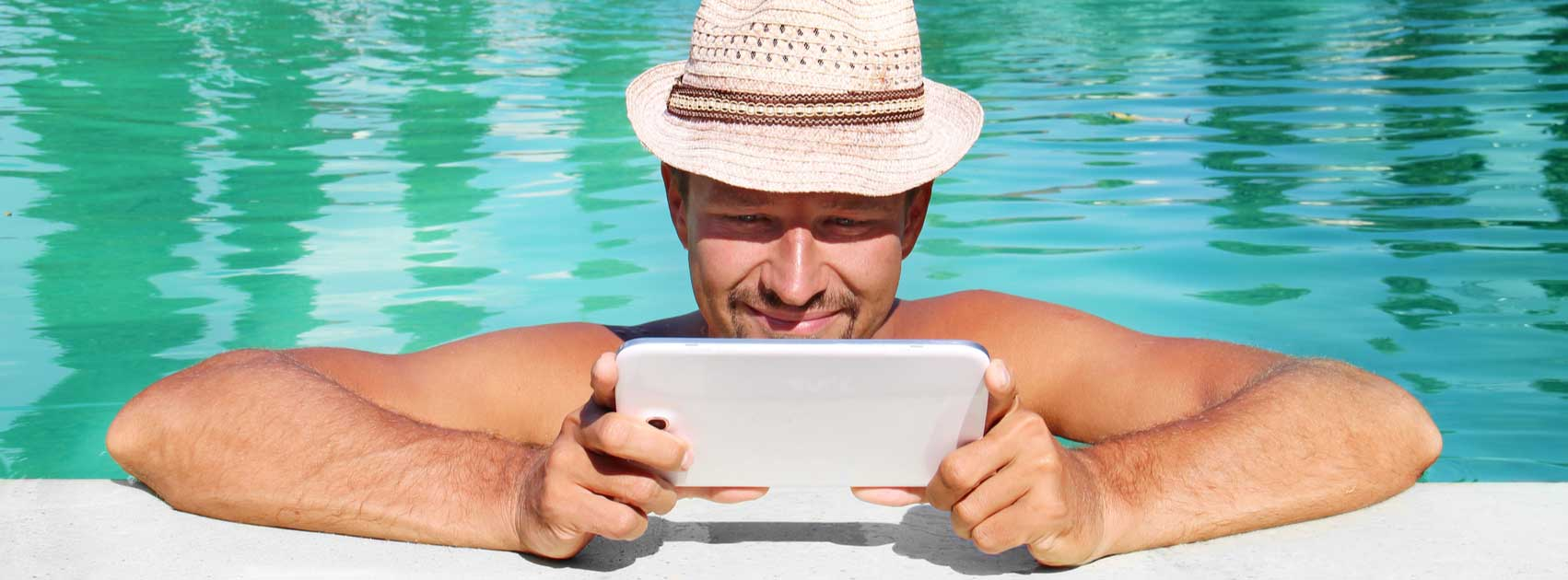 beautiful man by the pool with a tablet - Image