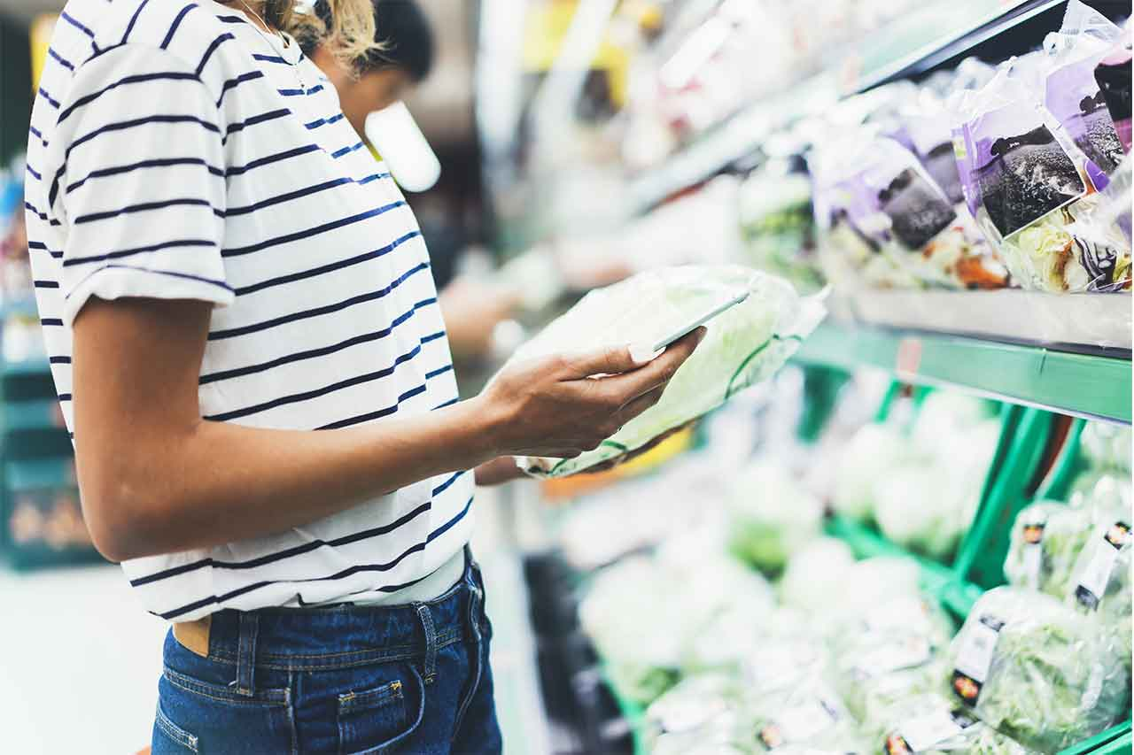 Lady looking at her phone while grocery shopping.