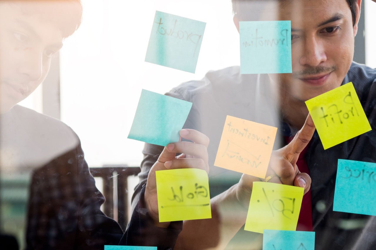 Business owner with his partner pointing to a sticky note.